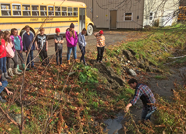 Harwood seventh-graders investigate stormwater catch basin to trace the path of water running off their classroom's roof. Photo: Friends of the Mad River