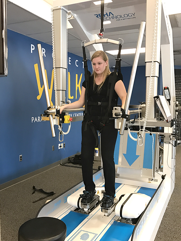 Lily Stilwell, Fayston, uses an assisted walking machine as part of her ongoing therapy following a spinal injury in October. Friends are raising funds to modify her home.