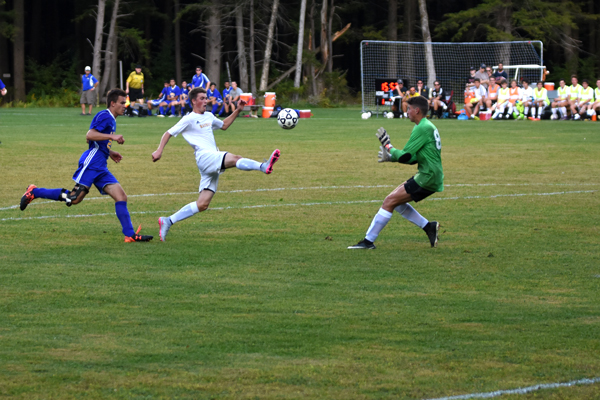 Harwood's Will Lapointe takes on the Lamoille goal keeper. Photo: Christopher Keating