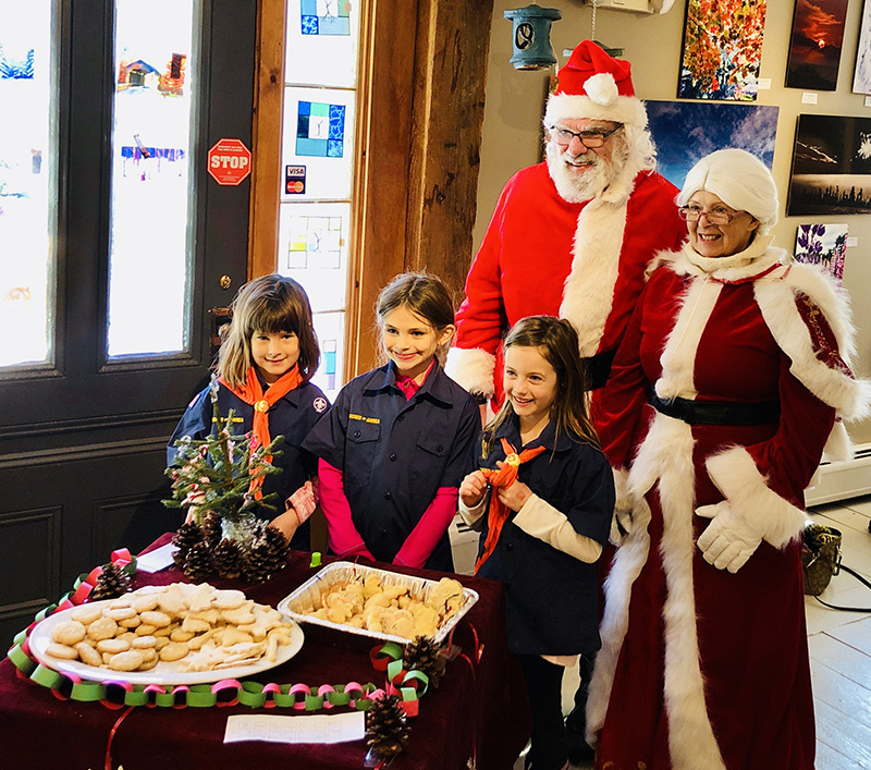 Girl Tiger Scouts and Santa and Mrs. Claus. The Girl Tiger Scouts made golden shortbread cookies.