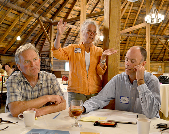 Workshop participants Jim Edgcomb(l) and Jon Jamieson (r) listen as consultant Patricia Floyd at the Economic Vitality Workshop at the Round Barn on August 13. Photo: Rachel Goff