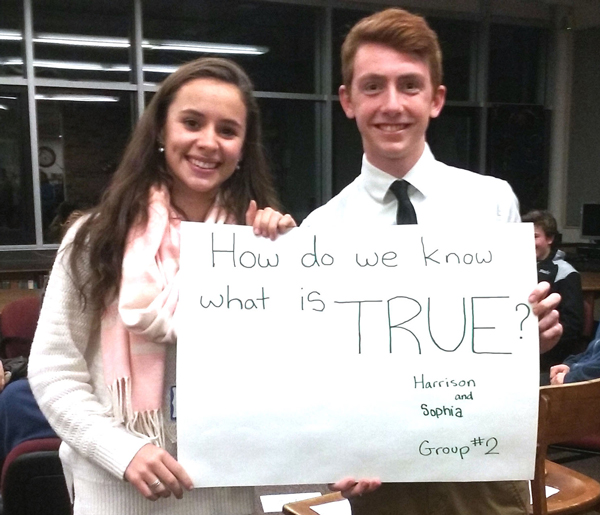 Harwood students Harrison and Sophia hold up one of the philosophical questions to help facilitate discussion at the Socrates Cafe. Photo: Tracy Brannstrom