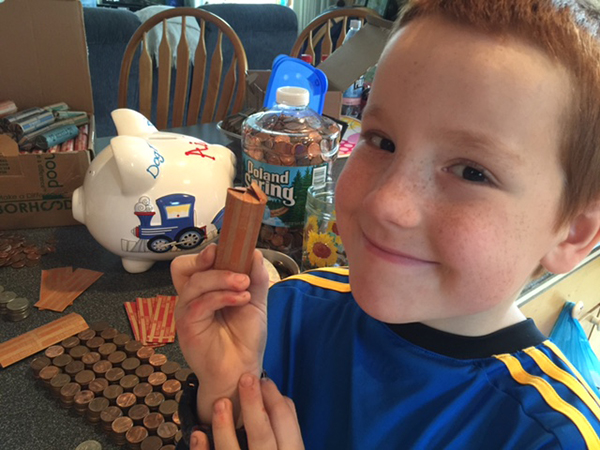 Aiden Heath rolls coins he has been saving since he was 4 years old after being diagnosed with type 1 diabetes at age 3. He plans to use the savings for a deposit on a service dog.