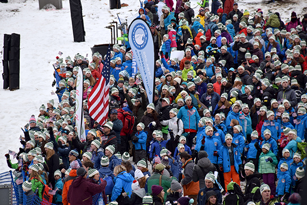Mad River Glen and GMVS/Sugarbush junior racers who are part of VARA(Vermont Alpine Racing Association) were part of the World Cup opening ceremonies. MRG coach Chris Downing waves an American Flag. Photo: Jeff Knight