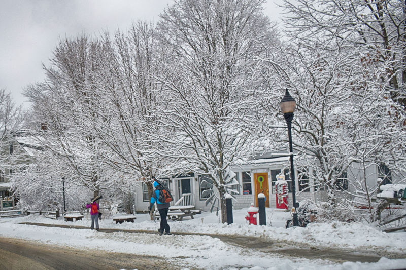 Skiers head to bus stop for a ride to the mountain. Photo: Jeff Knight