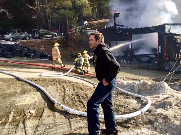 Tiger Baird looks on as firefighters battle the flames that destroyed his garage. Firefighters were able to save his adjacent residence. Photo: Andy Yeager