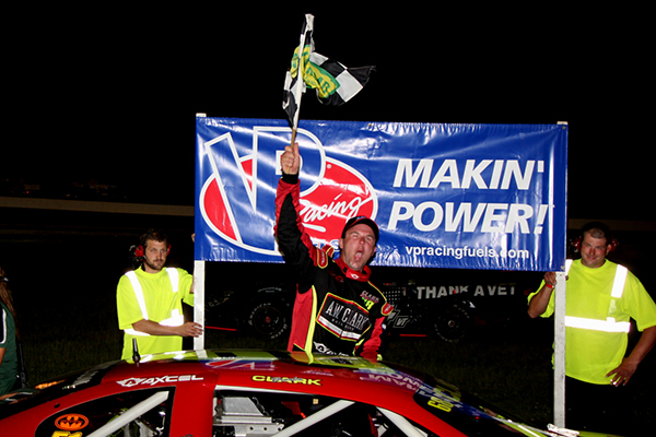 Brooks Clark, waves the checkered flag after winning the Governor's Cup race at Thunder Road on July 18