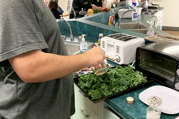 Senior Daniel Robinson prepares a kale dish for the fall harvest lunch at Harwood.