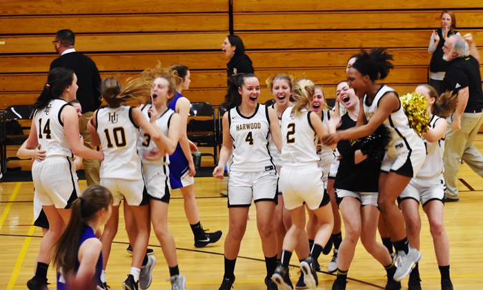 The Harwood girls' basketball team celebrates their OT win against Lake Region.
