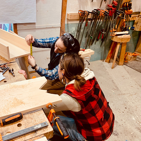 Instructor Lindley Brainard checks a measurement with one of her students in the Powertools for Women course recently held at Yestermorrow. Photo: Hadley Laskowski.