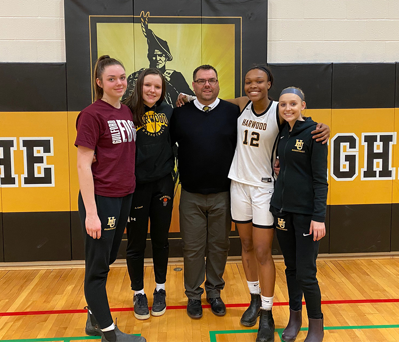Harwood girls' hoopsters pose with coach Tom Young on senior night. Left to right: Mia Cooper, Ashlyn Carst, coach Tom Young, Ella Gannon and Kennedy Wimble.