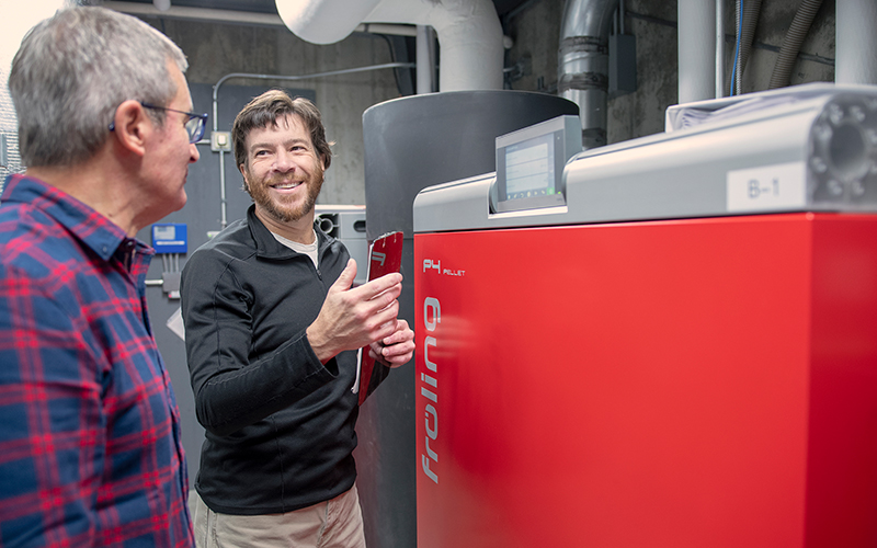 Dave Frank, Fayston, cofounder of SunWood Biomass, shows Mané Alves, founder of Vermont Artisan Coffee & Tea, the workings of a wood pellet boiler system installed at the coffee company's Route 100 facility in Waterbury Center.